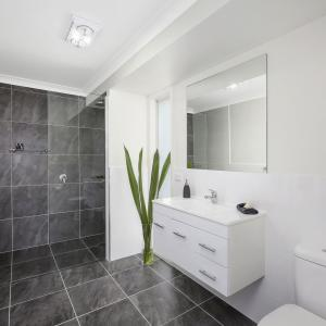 'The Angelica's' ensuite is a great size & the feature wall adds drama & interest as it flows up from the dark floor tiles